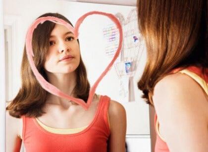 Tyttö piirsi peiliin sydämen ja katsoo itseään sen läpi