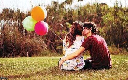 Pari suukottelee nurmikolla