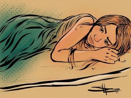 Tyttö makaa surullisena