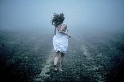 Nainen juoksee sumussa