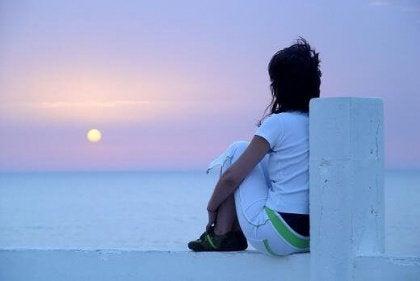 Nainen pitää huolta itsestään katselemalla auringonlaskua