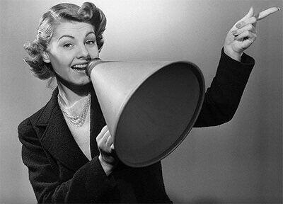 Nainen puhuu megafoniin ja ilmaisee tunteensa