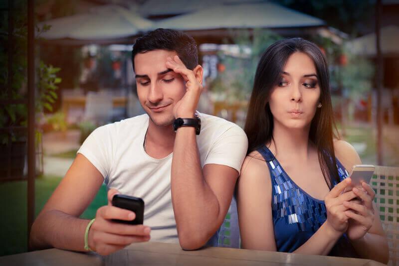 Pariskunta näplää puhelimiaan