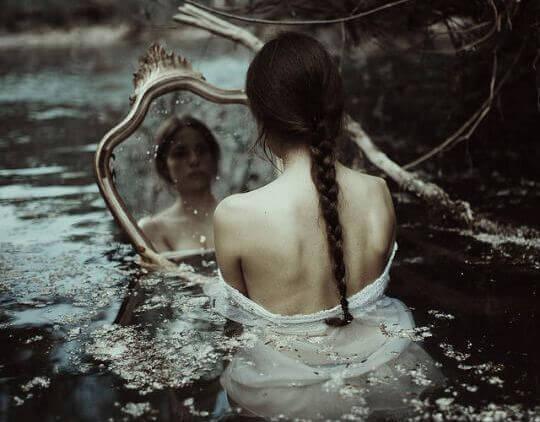 Tyttö katsoo itseään peilistä