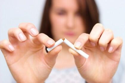 Nainen lopetta tupakoinnin ja katkaisee savukkeen
