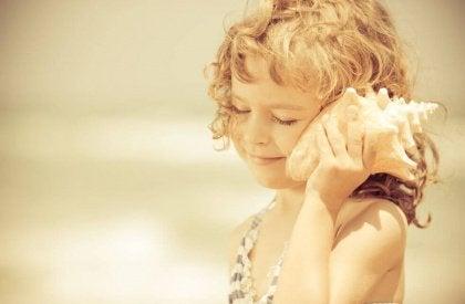 Tyttö kuuntelee simpukkaa