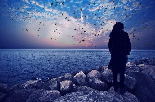 Nainen kivisellä rannalla
