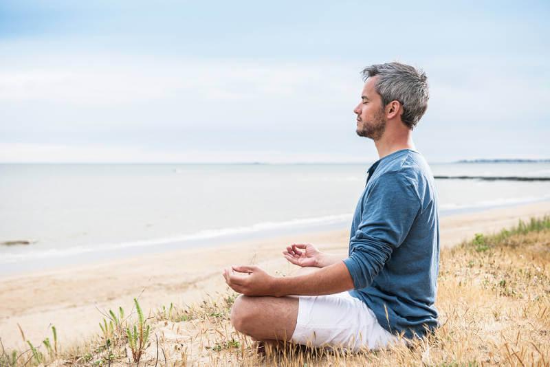 Mies meditoi rannalla