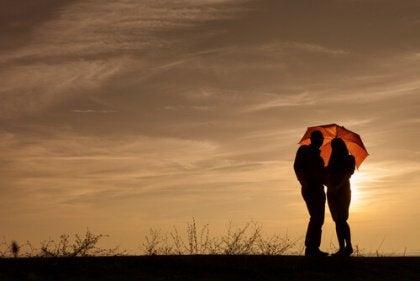 Pariskunta sateenvarjon alla