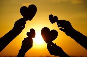 Neljä kättä pitelee sydämiä