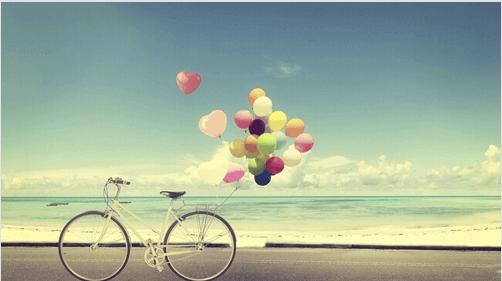 Pyörä ja ilmapallot rannalla