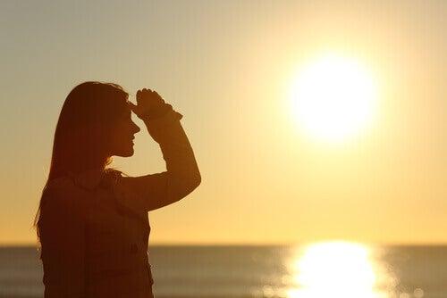 Nainen katsoo horisonttiin ja tuntee huolta