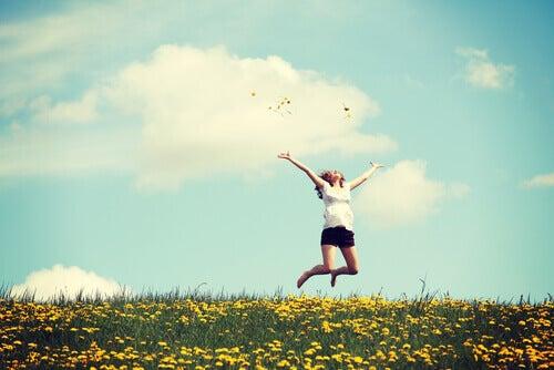 Nainen hyppii niityllä