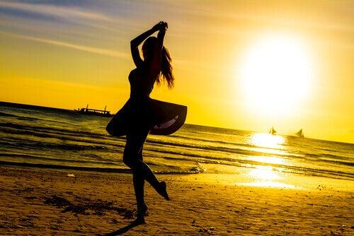 Nainen tanssii rannalla