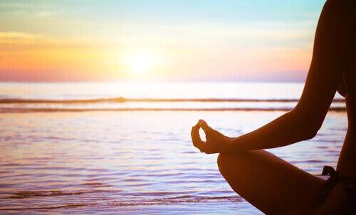 Nainen meditoi meren rannalla