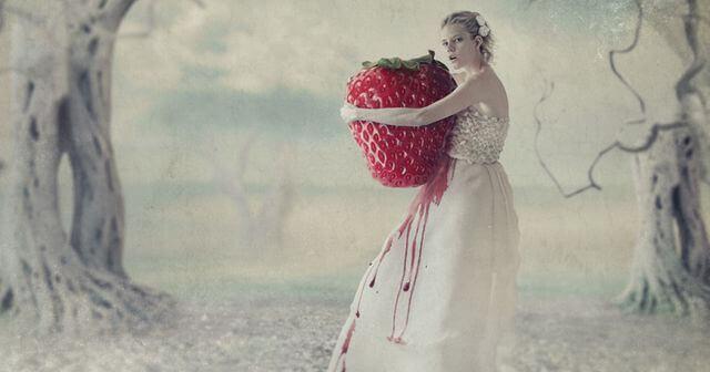 Nainen pitelee isoa mansikkaa