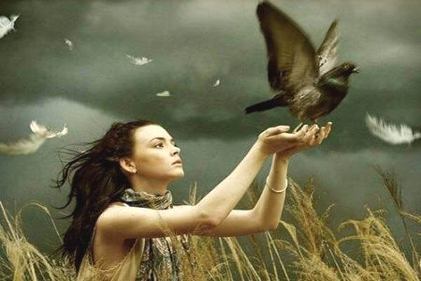 nainen vapauttaa linnun