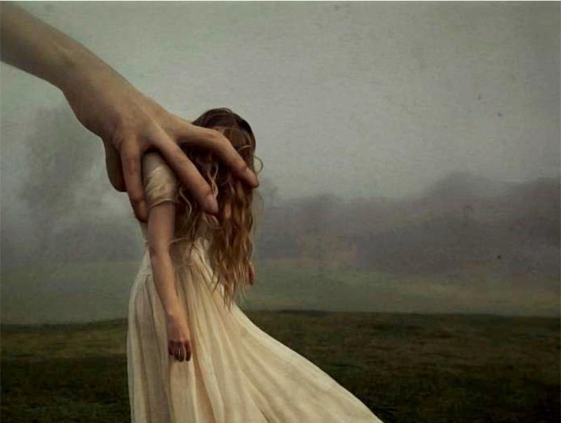 Suuri käsi pitelee naista