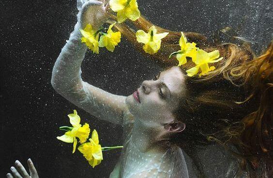 Nainen leijuu ylöspäin vedessä