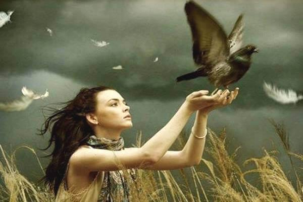 Nainen päästää linnun vapaaksi
