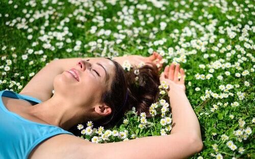 nainen makaa niityllä