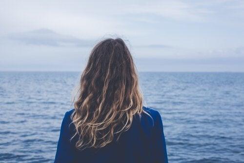 Nainen katselee merta päättää parisuhde