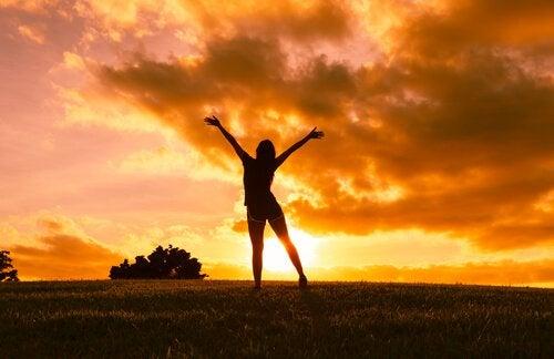 Optimistinen tyttö auringonlaskussa