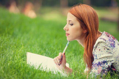 Tyttö kirjoittaa ulkona