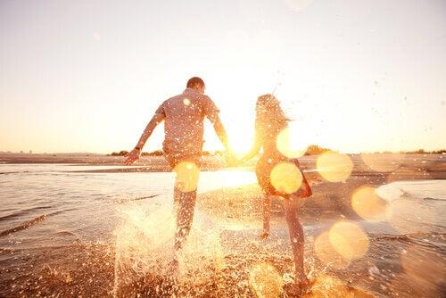 Pariskunta juoksee rantavedessä