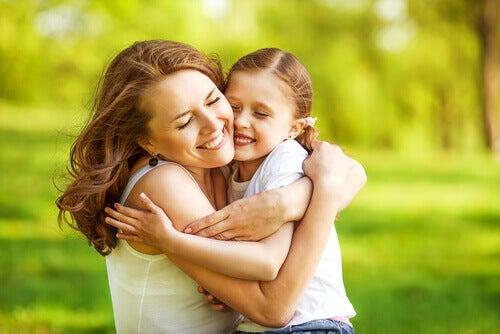 Fyysinen kontakti, äiti ja tyttö halaavat