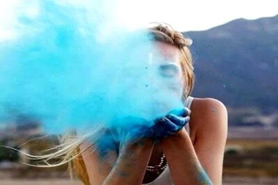 Tyttö puhaltaa sinistä maalia