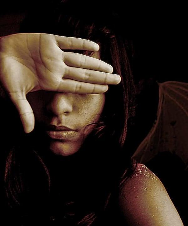 Nainen piiloutuu käden taa
