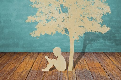 Poika lukee puun alla