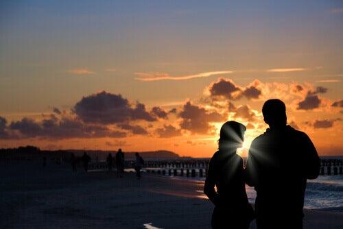 pariskunta meren rannalla auringonlaskussa