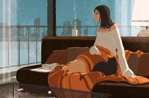 Nainen ja kissa sohvalla