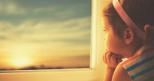 tyttö katsoo ikkunasta ulos