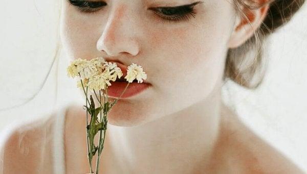 tyttö haistaa kukkaa