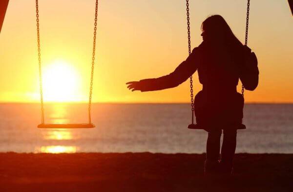 Nainen keinuu yksin auringon laskiessa