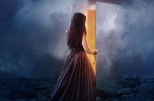 nainen sulkee tai aukaisee oven