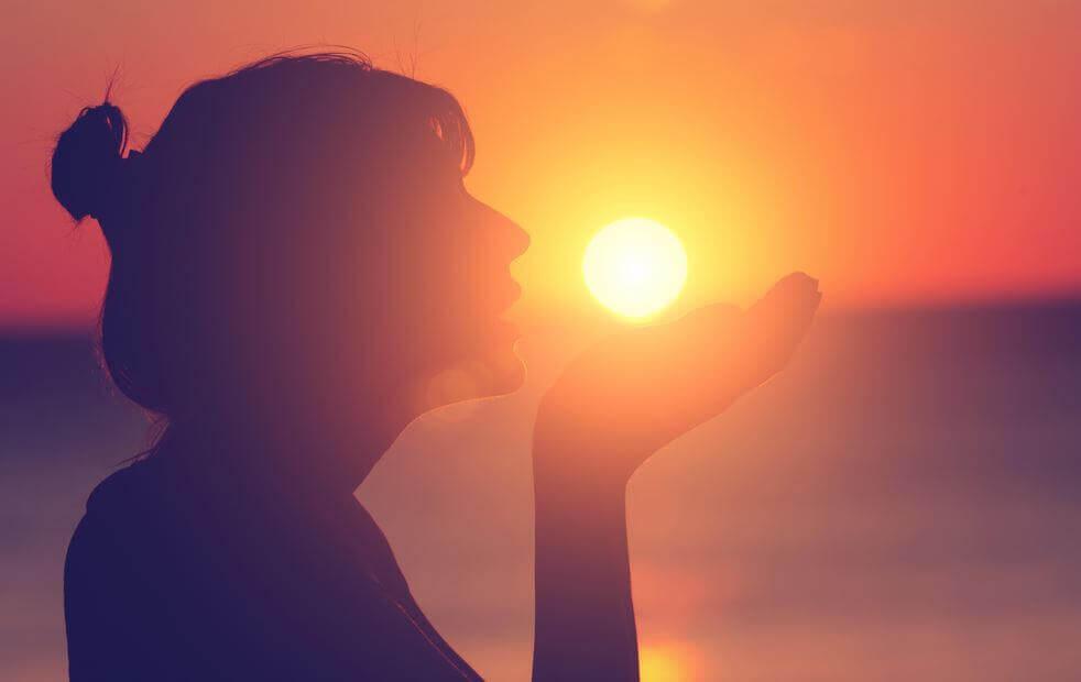 Nainen laskevan auringon valossa etsii mikä on kivun tarkoitus
