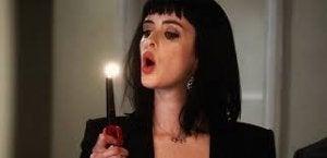 nainen puhaltaa kynttilän