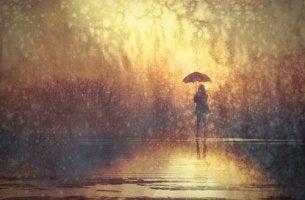 nainen seisoo yksin sateessa