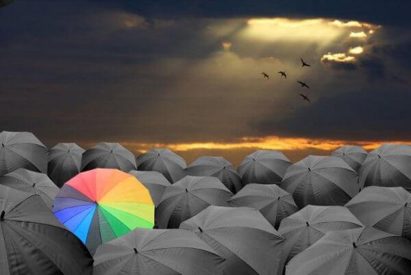 värikäs sateenvarjo mustien keskellä