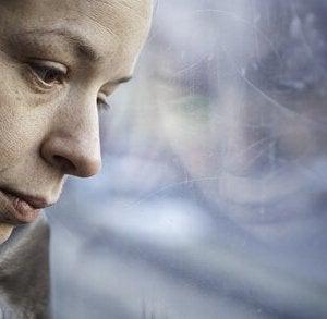 surullinen nainen katsoo ulos ikkunasta