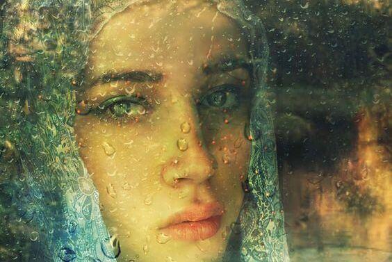 nainen katsoo ikkunan läpi