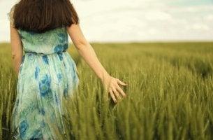 nainen kävelee heinäpellossa