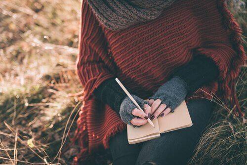 nainen kirjoittaa päiväkirjaan