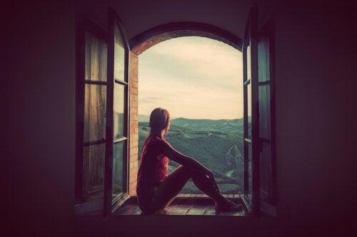 nainen istuu ikkunalaudalla