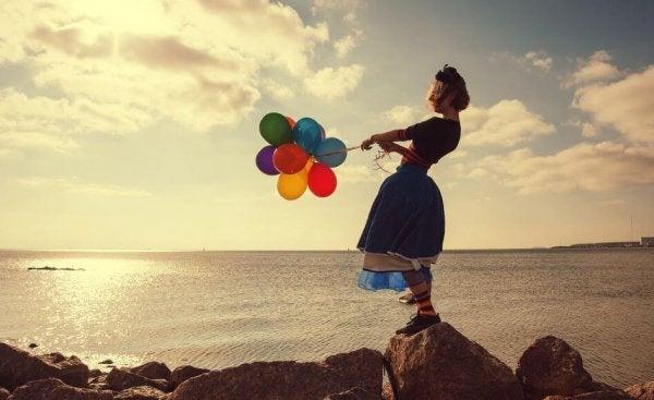 naisella ilmapalloja rannalla