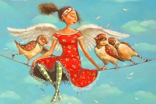 Nainen istuu lintujen kanssa